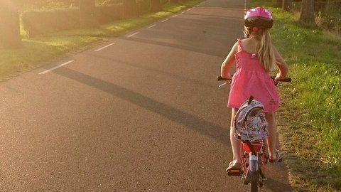 Bambina in bici con caschetto